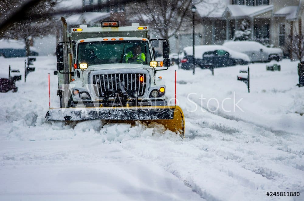 White truck with yellow snow plow blade clearing streets after heavy snowfall in urban area with driver wearing yellow safety vest